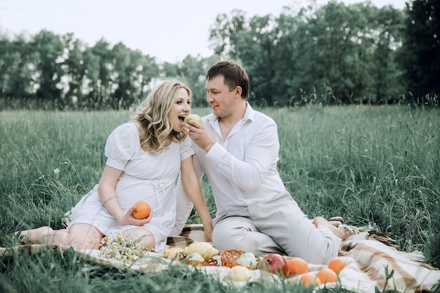 Happy man with his pregnant wife at picnic on summer day