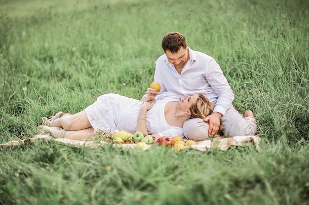여름 날에 잔디밭에 쉬고 임신 한 아내와 함께 행복 한 사람. 가족 행복의 개념