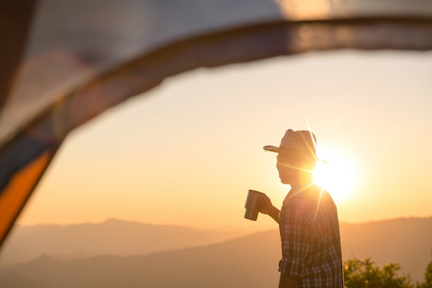 Happy man with holding coffee cup stay near tent around mountains