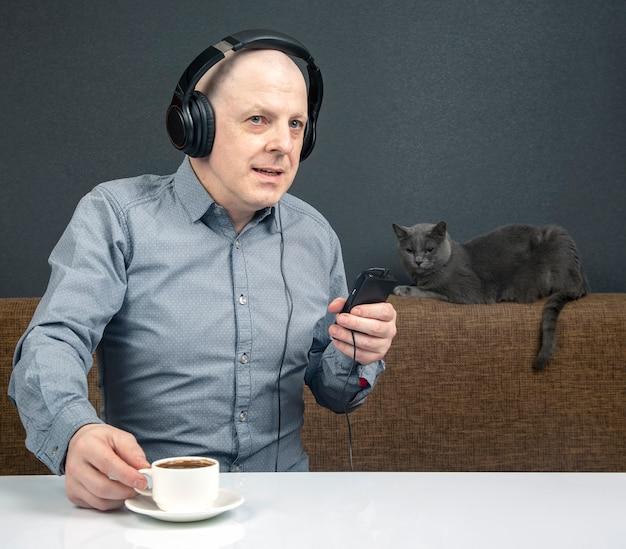 휴대용 헤드폰을 끼고 있는 행복한 남자는 플레이어를 사용하여 음악을 듣습니다.