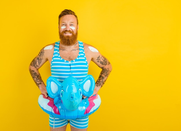 코끼리와 함께 풍선 도넛을 들고 수영할 준비가 된 행복한 남자 프리미엄 사진