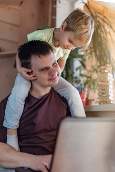 Happy man with joyful children using laptop and earphone during his home working while sitting on sofa at home, home office with together with children, life during quarantine