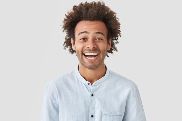 Uomo felice con espressione gioiosa, ha un sorriso perfetto e denti bianchi, ride di qualcosa di divertente