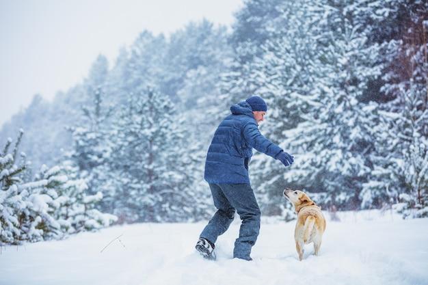 Счастливый человек с собакой лабрадора ретривера играет в зимнем снежном лесу