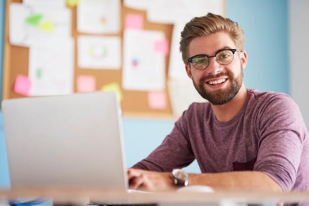 Счастливый человек с портативным компьютером в офисе