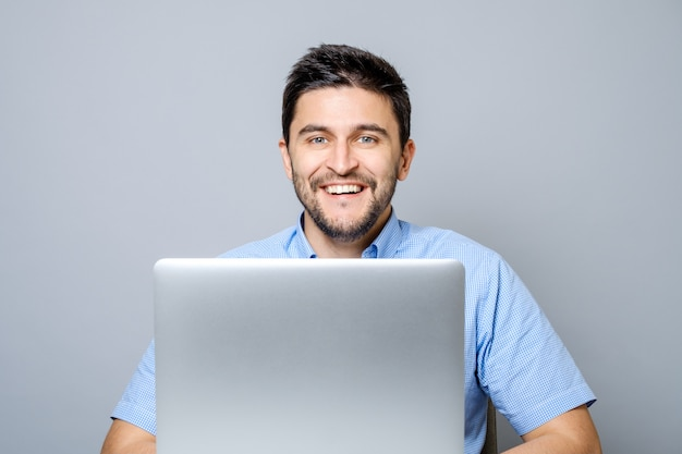 Happy man with laptop computer isolated on gray