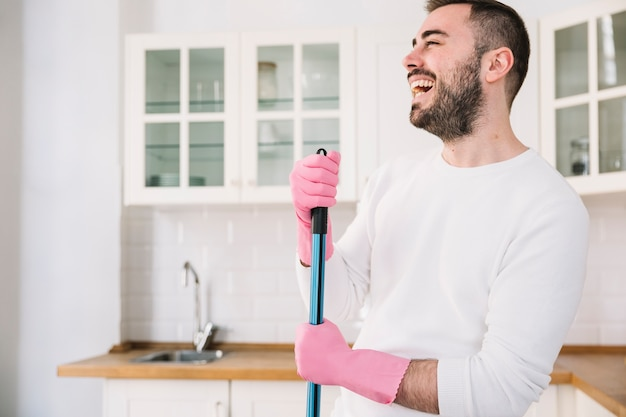 Happy man with mop on kitchen
