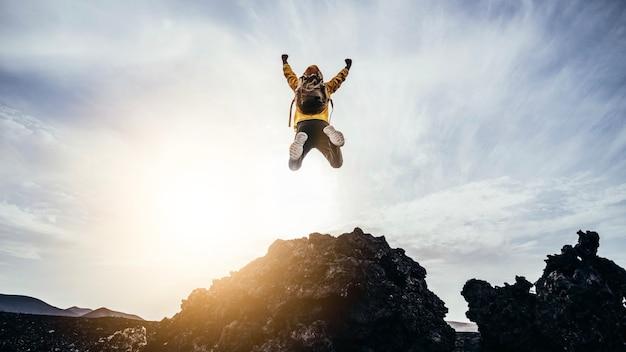 Счастливый человек с распростертыми объятиями прыгает на вершину горы hiker с рюкзаком, празднуя