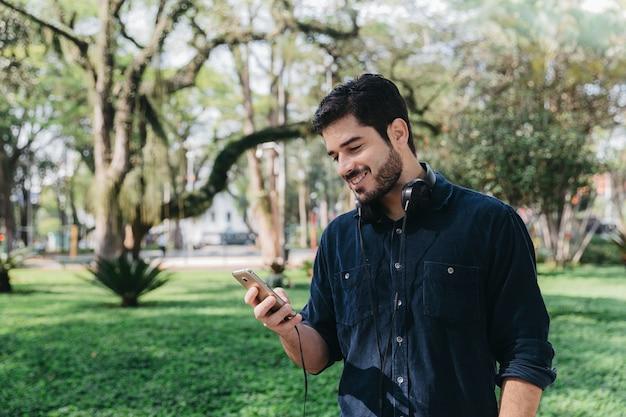 緑の公園の電話で幸せな男