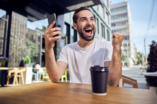 스마트 폰 및 커피 카페에 앉아 행복 한 사람을 닫습니다.