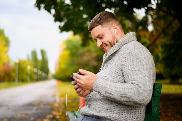 Happy man with smartphone and earphones on a bench