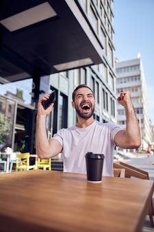 커피와 함께 카페에 앉아 스마트 폰으로 행복 한 사람을 닫습니다.