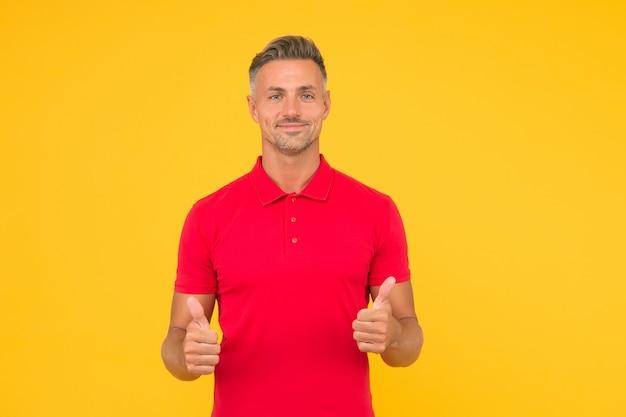 빨간 티셔츠에 세련된 수염 머리를 한 행복한 남자는 만족스러운 손 제스처를 노란색으로 엄지손가락을 보여줍니다.