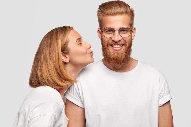 濃厚な髭を生やした幸せな男、ガールフレンドからのキスを受け取り、一緒にデートし、愛と前向きさを表現する