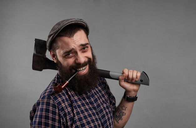 Happy man with tobacco pipe in mouth and with axe in hand. smiling attractive guy with beard on grey background in studio. satisfaction of life concept.