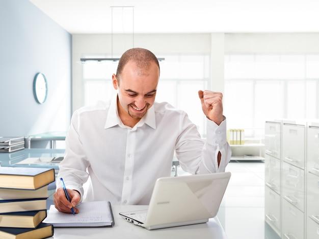 現代のオフィスで白いラップトップを持つ幸せな男