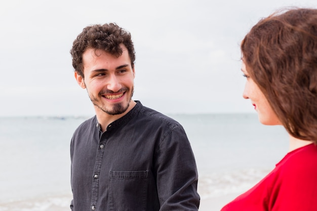 Happy man with woman on sea shore