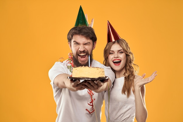 Happy man and woman in a cap celebrating a birthday on a yellow background with a cake in their hands. high quality photo
