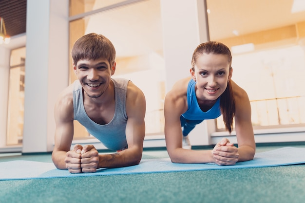 Happy man and woman doing sports stand on mat