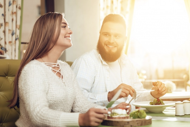 Happy man and woman have lunch in a restaurant