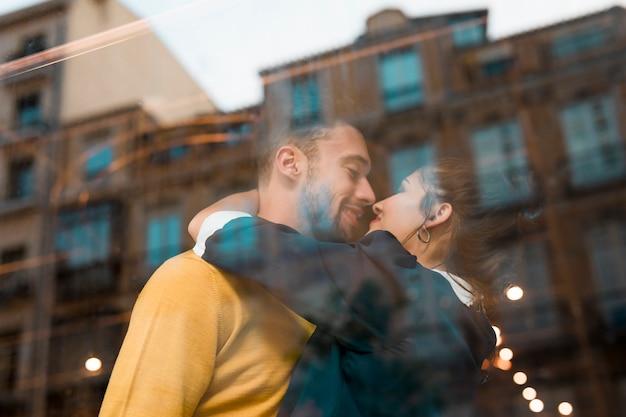 Happy man and woman hugging in restaurant near window