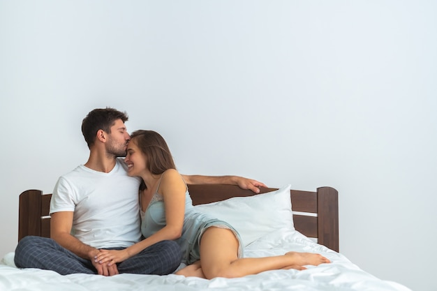 The happy man and a woman kissing on the bed on the white background