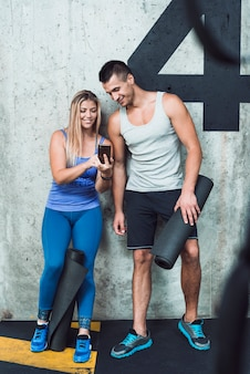 Happy man and woman looking at cellphone in gym