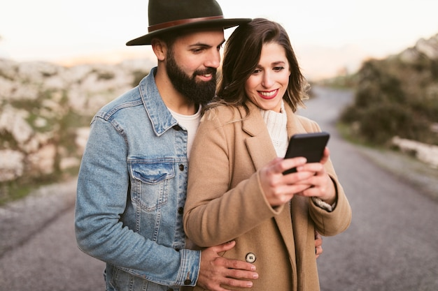 Happy man and woman looking on phone on road