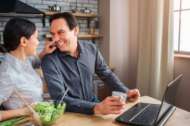 Happy man and woman sit together in kitchen she touch his nose. guy smile. he hold white cup.