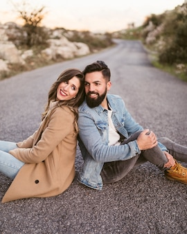 Happy man and woman sitting on road