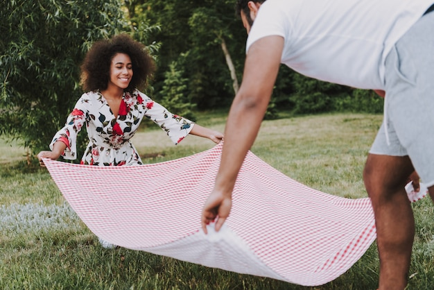Happy man and woman spread blanket together