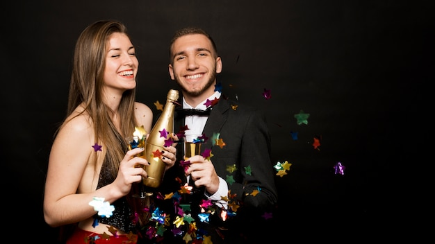 Happy man and woman with bottle and glasses of drinks between confetti