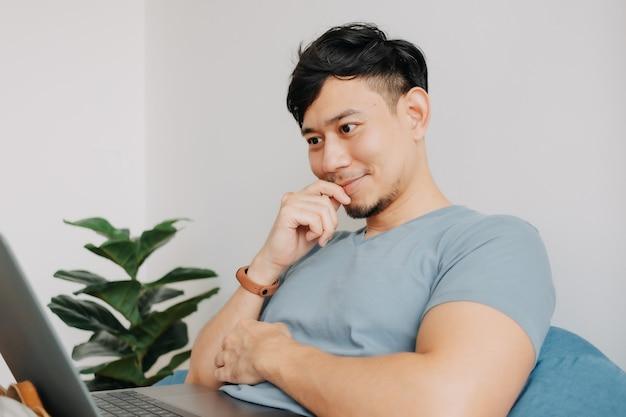 幸せな男は、自宅で仕事をしている間、コンピューターのラップトップで働きます