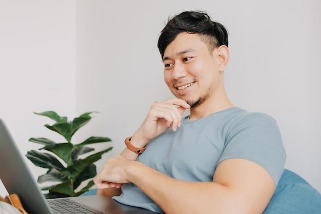 幸せな人は家にいる間コンピュータのラップトップで仕事をする家で仕事をする