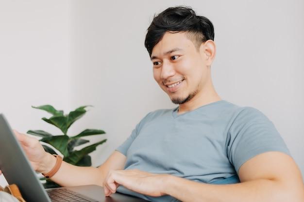 Счастливый человек работает с компьютерным ноутбуком, оставаясь дома, работает дома