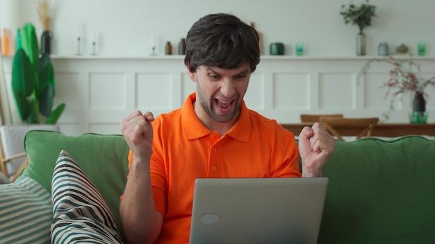 Счастливый человек работает на компьютере дома и празднует победу с поднятыми руками и кричит