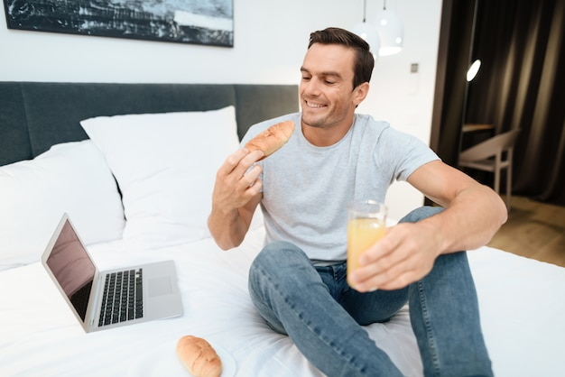 Happy man working and having breakfast in bed