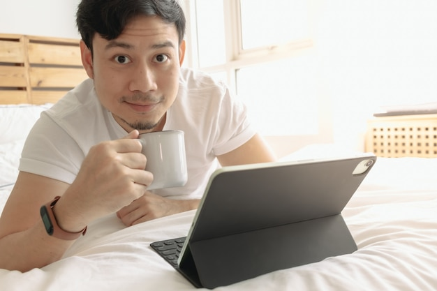 Happy man works on his tablet with a cup of coffee on the bed
