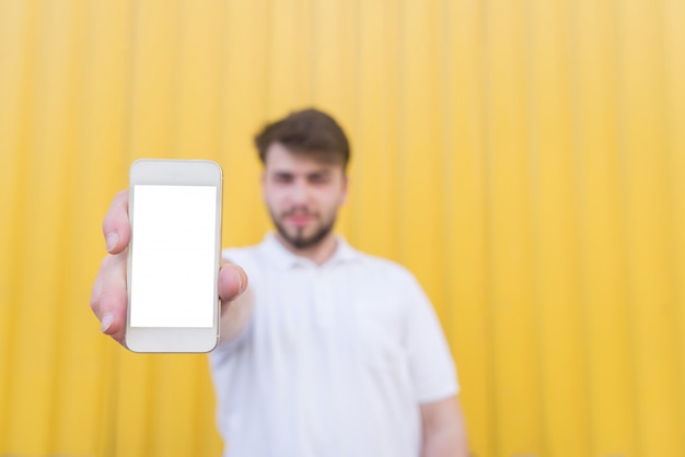 Happy man on a yellow background with a smartphone in his hands