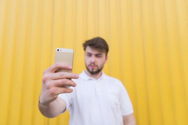 Happy man on a yellow wall makes for selfie smartphone in hand. focus on the smartphone