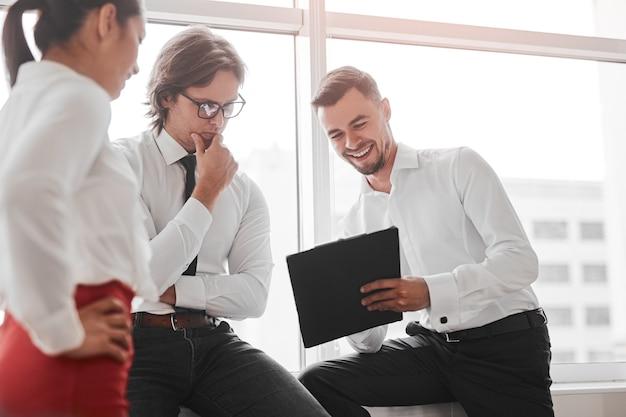 직장에서 창 근처의 비즈니스 프로젝트를 논의하는 동안 남성과 여성 동료에게 클립 보드의 데이터를 보여주는 행복한 관리자