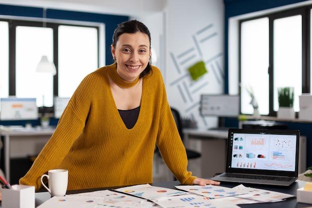 Счастливый менеджер, стоя в офисе запускающей компании, улыбается и смотрит в камеру. исполнительный предприниматель, руководитель-менеджер, постоянно работающий над проектами.