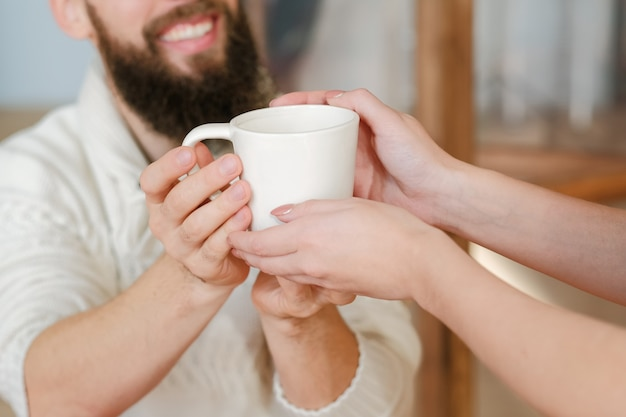 행복한 결혼. 사랑, 보살핌 및 조화. 사랑하는 남편을 위해 뜨거운 음료와 함께 머그잔을주는 아가씨.
