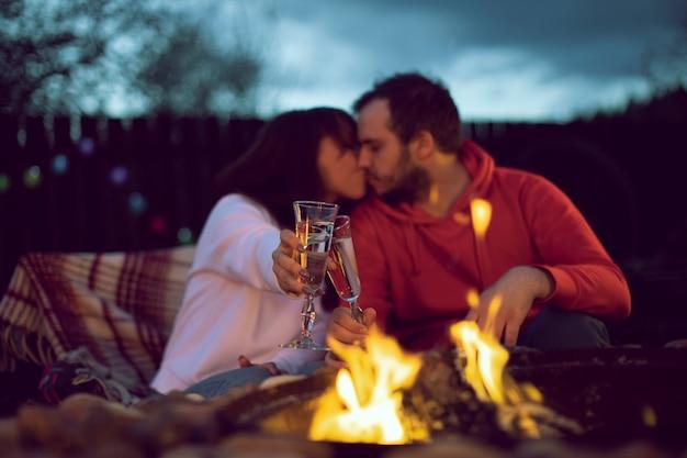 Счастливая супружеская пара у костра празднует годовщину свадьбы, пьет шампанское и целуется