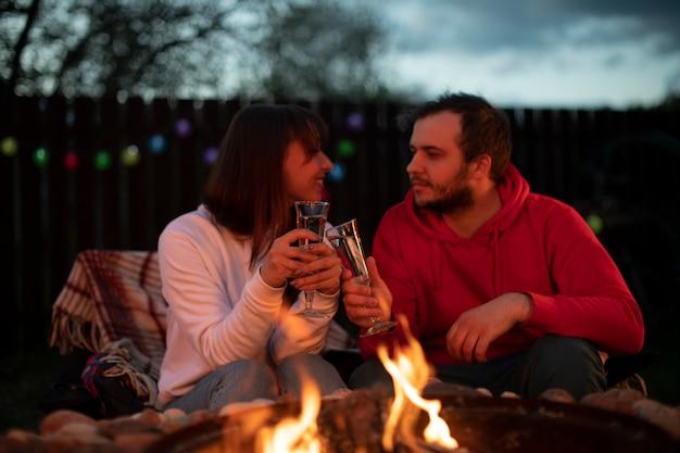 Счастливая семейная пара у костра отмечают праздник и пьют шампанское