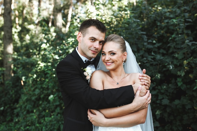 Happy married couple embracing in forest