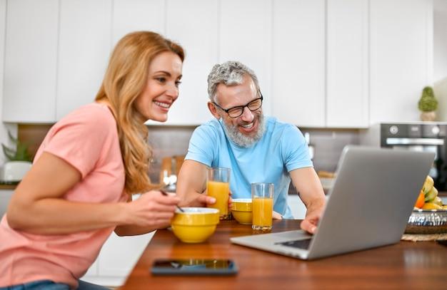 행복한 부부는 아침을 먹고 부엌에서 노트북을 사용하여 즐거운 시간을 보냅니다.
