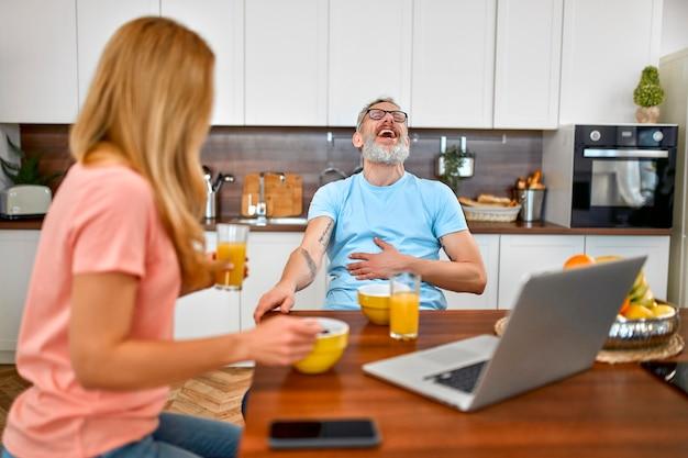 행복 한 부부는 아침 식사를하고 부엌에서 노트북을 사용 하여 재미 있습니다.