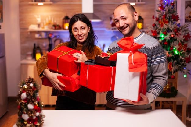 Felice coppia sposata che tiene un regalo regalo segreto con un nastro su di esso