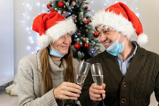 보호 마스크에 행복 한 부부는 크리스마스 샴페인을 마신다.